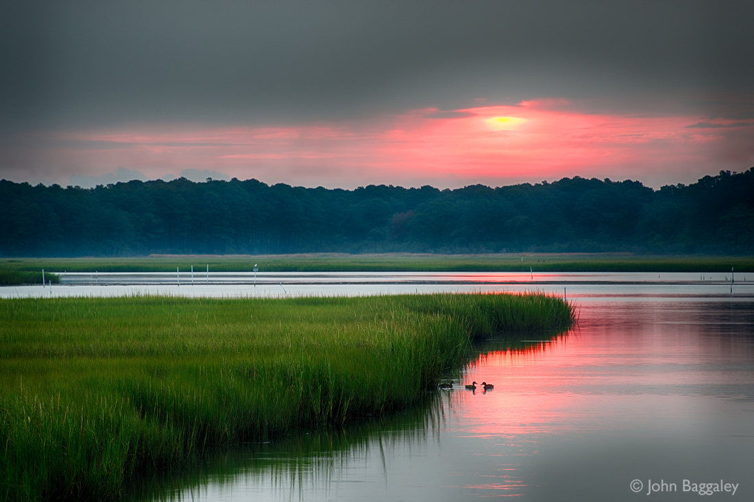 Photo by John Baggaley of a summer sunrise over Assateague Island (Chincoteague National Wildlife Refuge) in Virginia.