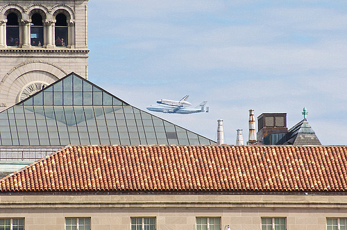 Space Shuttle Discovery flies by the Old Post Office Pavilion