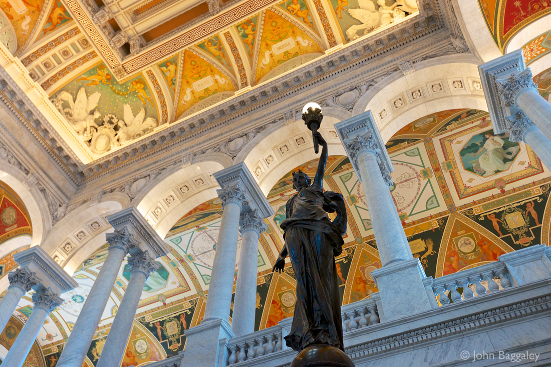 A bronze statue of a female figure holding a torch of electric light inside the Great Hall of the Thomas Jefferson Building of the Library of Congress.