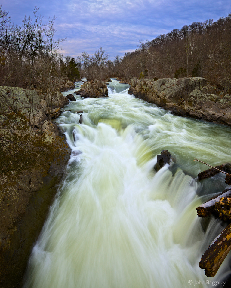 Heavy clouds hang over rushing water in an off-shoot of the Potomac River at Great Falls Park in Maryland.