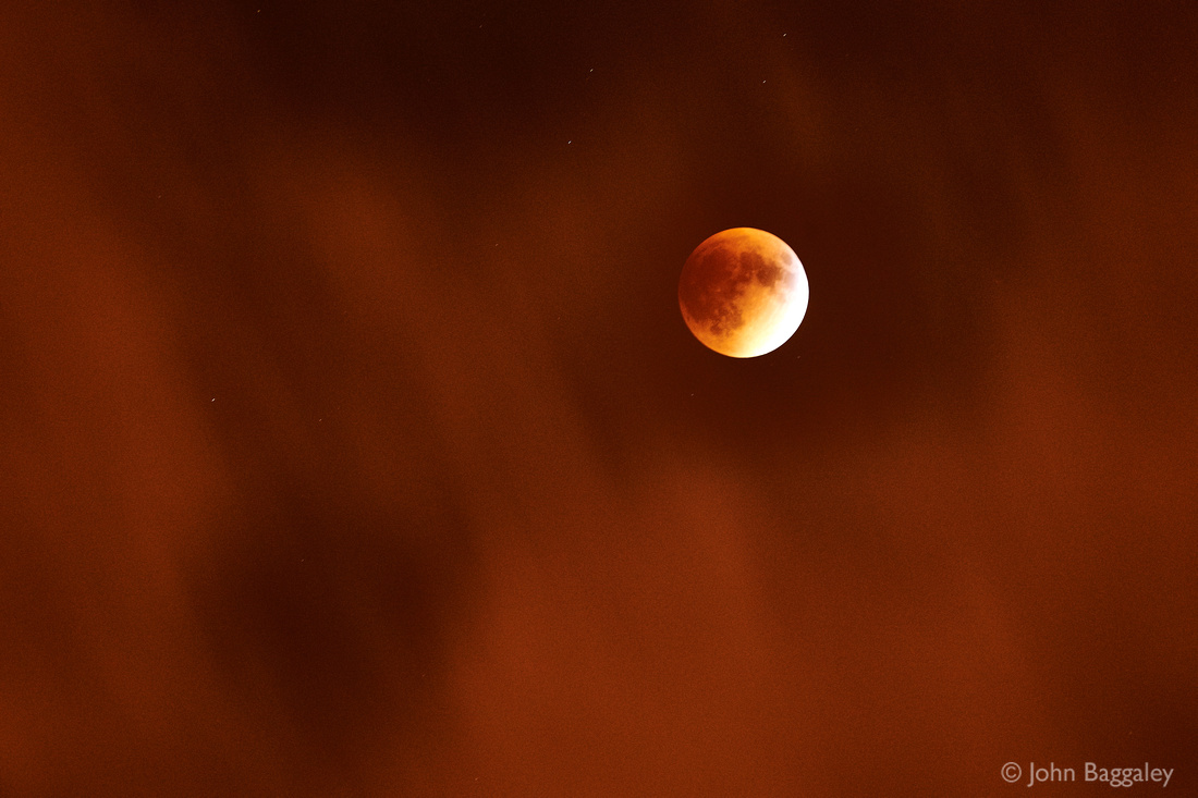 Supermoon Eclipse Under a Veil of Clouds