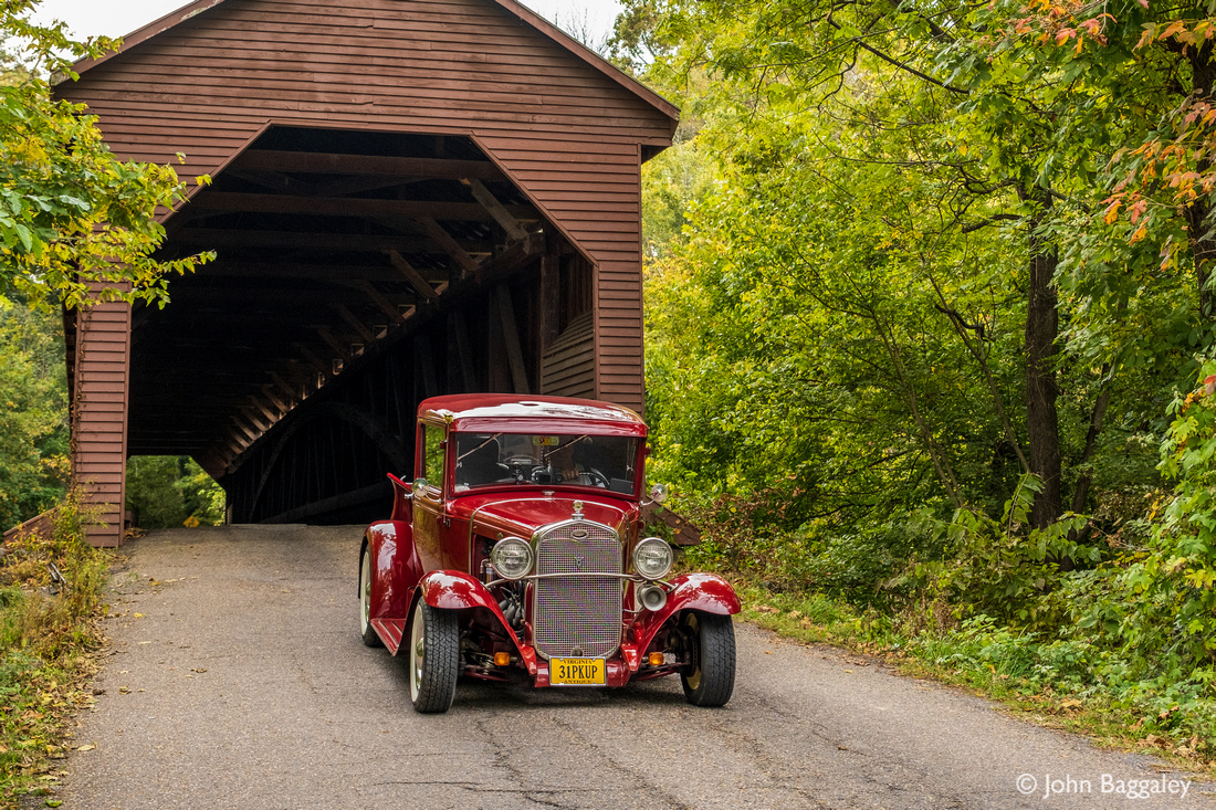 A covered bridge and a red antique truck